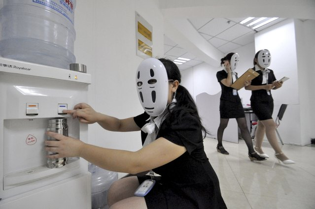 "Staff wearing masks during a work day at a property service company specializing in leased office space in Handan in northern China's Hebei province Tuesday, July 14, 2015. The company holds a monthly relaxation day at the office using various themes such as a ""faceless"" day when workers wear masks with the idea that they don't have to fake their facial expression through the day. (Photo by Chinatopix Via AP Photo)"