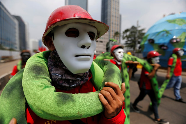 Indonesian workers wear masks as they march during a May Day rally in Jakarta, Indonesia on May 1, 2017. (Photo by Reuters/Beawiharta)