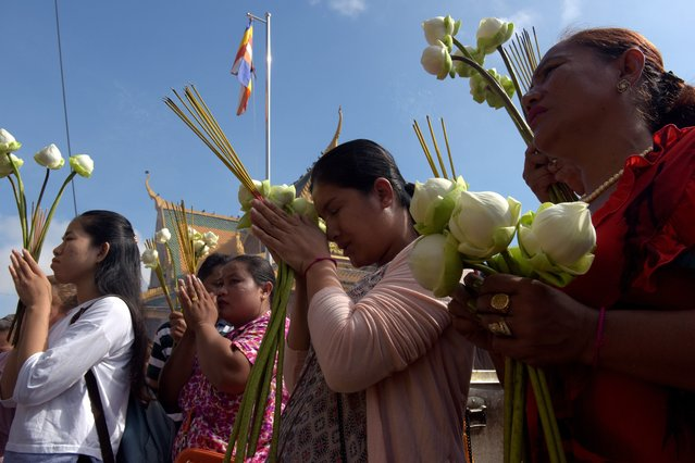 "Cambodian women pray in front of a shrine out side the Royal Palace in Phnom Penh on May 10, 2017. Cambodian celebrate 2,561 years of Buddha, called ""Visak Bochea"", that is the date of Buddha's birth, enlightenment and death on the day of the full moon. (Photo by Tang Chhin Sothy/AFP Photo)"