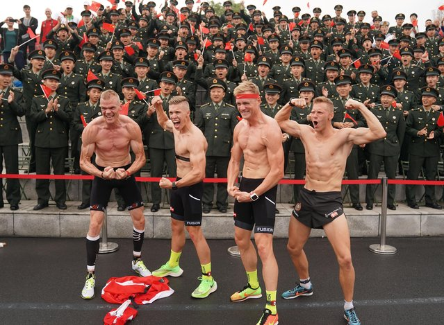 Athletes of Denmark pose for photo with soldiers on the stands after the cross country of men's individual of military pentathlon during the 7th Military World Games in Wuhan, Hubei Province, China on October 23, 2019. (Photo by Xinhua News Agency/Rex Features/Shutterstock)