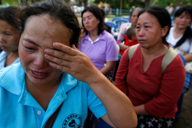 Malawian Saw-wa, 33, (L) who lost her daughter, cries near a burnt building at the Pitakkiat Wittaya School in the northern province of Chiang Rai, Thailand, May 23, 2016. (Photo by Athit Perawongmetha/Reuters)