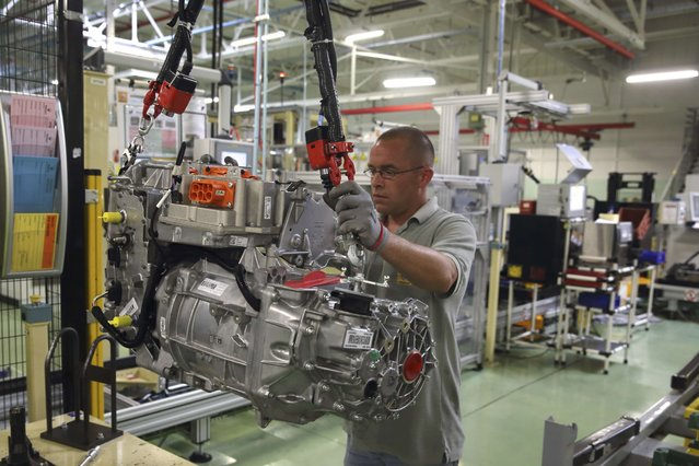 A employee handles the new R240 electric engine by French carmaker Renault for their Zoe model automobile at their factory in Cleon, Western France, July 20, 2015. The Renault plant constructs the R240 electrical car engine, with an autonomy of 240 kilometres, for its Zoe line of automobiles. The plant has a current production capacity of 50,000 engines that can be increased to 100,000 units. (Photo by Philippe Wojazer/Reuters)