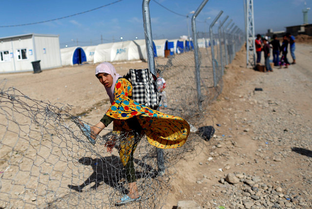 A displaced Iraqi girl climbs a fence to get inside Hammam al-Alil camp south of Mosul, Iraq, April 27, 2017. (Photo by Danish Siddiqui/Reuters)