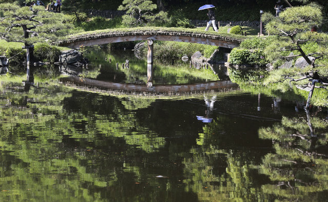 A woman with a parasol crosses a bridge on the pond at Kiyosumi Gardens in Tokyo, Friday, May 19, 2017. The temperature in Tokyo soared to 26.3 degrees Celsius (79 degrees Fahrenheit). (Photo by Koji Sasahara/AP Photo)