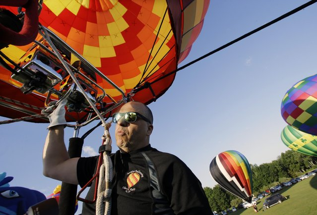 Mike Hernendez, of Glens Falls, N.Y., controls his hot air balloon in the early morning during the 33rd annual QuickChek New Jersey Festival of Ballooning at Solberg Airport Friday, July 24, 2015, in Readington, N.. (Photo by Mel Evans/AP Photo)