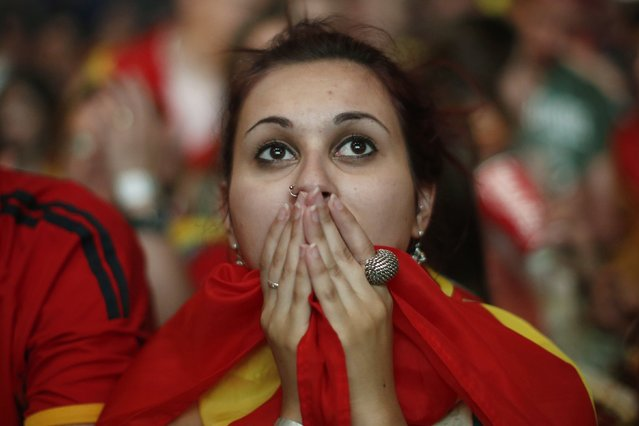 A Spanish soccer fan covers her face as she watches on a giant display a World Cup soccer match between Spain and Chile, in Madrid, Spain, Wednesday, June 18, 2014. (Photo by Andres Kudacki/AP Photo)