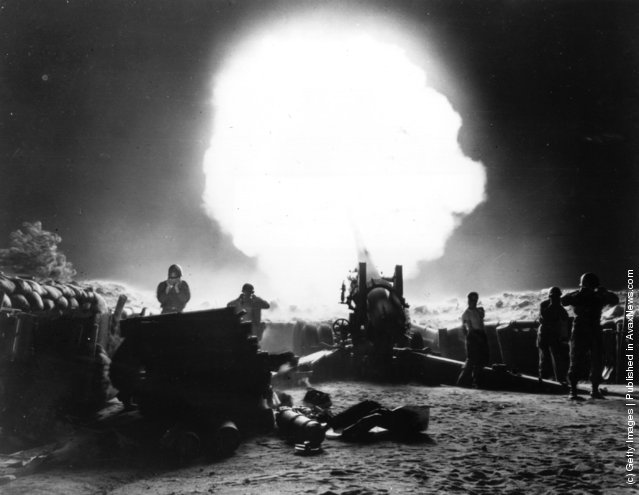 A dramatic shot of 155mm Howitzer fire during night action in the Korean War, 1952