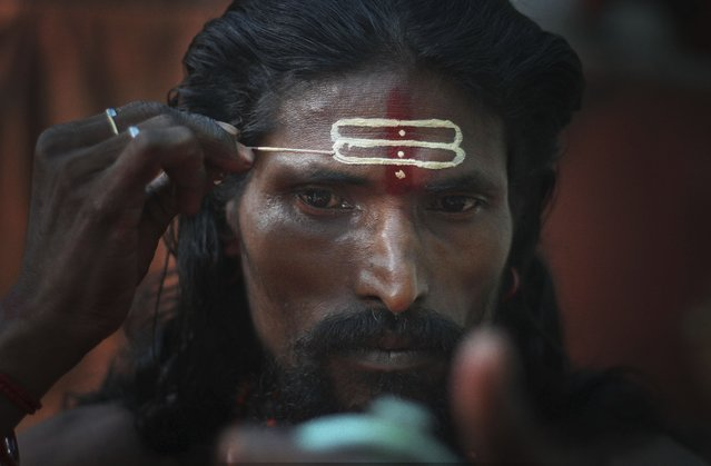 An Indian Hindu holy man applies sandalwood paste on his forehead looking at a mirror during the Ambubasi festival at the Kamakhya Hindu temple in Gauhati, India, Sunday, June 22, 2014. The annual festival where hundreds of holy men from an esoteric form of Hinduism, gather to perform rituals at the temple begins on June 22. (Photo by Anupam Nath/AP Photo)