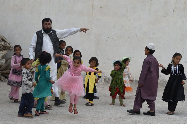 In this photograph taken on March 23, 2016, Pakistani father Sardar Haji Jan Mohammad Khilji plays with some of his children at his residence in Quetta. A Pakistani father of 35 is now searching for a fourth wife as he romps towards his goal of 100 children, a dubious ambition in the conservative Muslim country where polygamy is rare but still practiced. (Photo by Banaras Khan/AFP Photo)