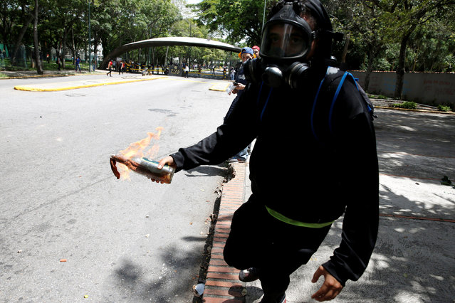 A demonstrator prepares to throw a molotov cocktail towards riot police officers during a protest called by university students against Venezuela's government in Caracas, Venezuela, June 9, 2016. (Photo by Carlos Garcia Rawlins/Reuters)