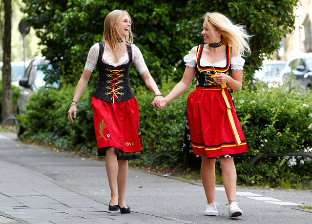 Models pose in the street wearing traditional Bavarian dresses known as a Dirndl, in the national colours of Germany for Euro 2016, in Munich, Germany, June 10, 2016. (Photo by Michaela Rehle/Reuters)
