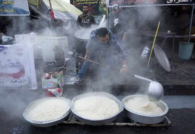 In this photo taken Sunday, December 8, 2019, a volunteer chef prepares rice to be served to Iraqi protesters as part of a free meal, at the center of Baghdad, Iraq. In Baghdad's Tahrir Square, there are the anti-government protesters demonstrating for a better future for Iraq, and there are the volunteers who feed them. From stuffed lamb and fish, to the giant pots of soups and rice to the plates of lentils and beans, there is no shortage of food to go around. Volunteers from the capital and southern provinces cook traditional dishes that reflect the country's rich cuisine and bring protesters together. (Photo by Nasser Nasser/AP Photo)