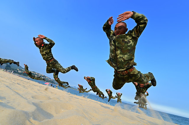 Frontier soldiers take part in an exercise on a beach August 4, 2015. Heat wave sustained in Guangdong, where ground temperature got close to 60 Celsius degress by the sea. (Photo by Mao Siqian/Xinhua Press/Corbis)