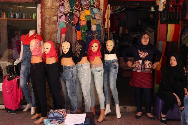 Women stand outside their shop near veils displayed on mannequins for sale during the holy month of Ramadan in Tyre old city, southern Lebanon June 12, 2016. (Photo by Alia Haju/Reuters)