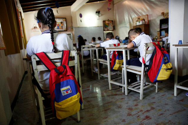 Backpacks with the colours of the Venezuelan national flag hang on chairs during a class at an improvised classroom above a state-run supermarket, which is part of state school Monsenor Marco Tulio Ramirez Roa, in La Fria, Venezuela, June 1, 2016. (Photo by Carlos Garcia Rawlins/Reuters)