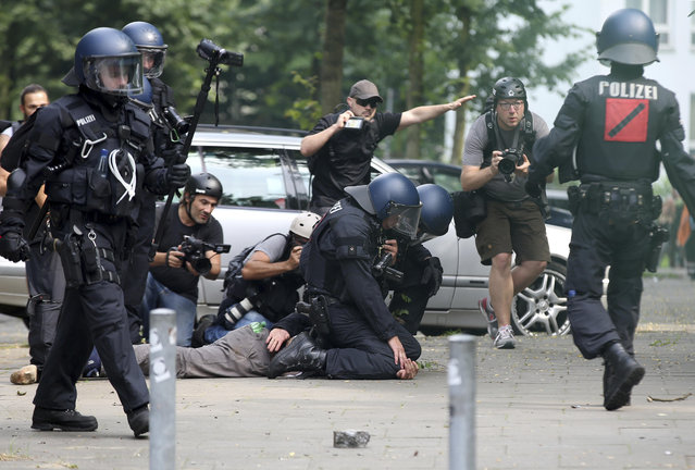 Police detain a demonstrator watched by journalists during a protest on the first day of the G-20 summit in Hamburg, northern Germany, Friday, July 7, 2017. The leaders of the group of 20 meet July 7 and 8. (Photo by Bodo Marks/DPA via AP Photo)