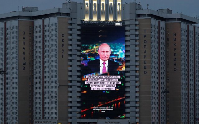 """An electronic screen, installed on the facade of a hotel, shows an image of Russian President Vladimir Putin and a quote from his annual address to the Federal Assembly in Moscow, Russia on January 15, 2020. The quote reads: """"I propose to provide free hot meals to all elementary school students from grades 1 to 4"""". (Photo by Evgenia Novozhenina/Reuters)"""