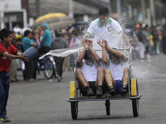 """In this Saturday, August 8, 2015 photo, a youth throws water on porters, known as """"cargadores"""", from the Mayorista Market as they compete in the team category of an organized race using their work tricycles, at the market in Quito, Ecuador. The three decade old market has over 1,000 vendors, many of them indigenous, and supplies goods to other markets in the capital. The winners were awarded new tricycles. (Photo by Dolores Ochoa/AP Photo)"""