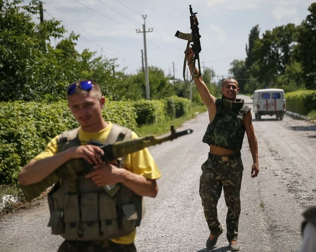 """Ukrainian soldiers stand guard in the eastern Ukrainian town of Seversk July 12, 2014. Ukrainian war planes bombarded separatists along a broad front on Saturday, inflicting huge losses, Kiev said, after President Petro Poroshenko said """"scores and hundreds"""" would be made to pay for a deadly missile attack on Ukrainian forces. (Photo by Gleb Garanich/Reuters)"""