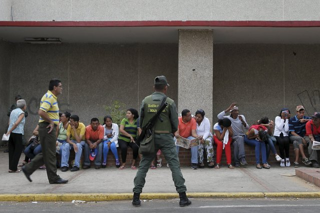 A soldier stands guard next to people waiting in a line for opening time to buy staple items outside a supermarket in Maracaibo August 8, 2015. (Photo by Isaac Urrutia/Reuters)