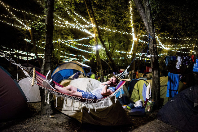 Lying in a hammock a young man smokes during the 23rd Sziget (Island) Festival on Shipyard Island, Northern Budapest, Hungary, early 14 August 2015. The festival is one of the biggest cultural events of Europe, offering art exhibitions, theatrical and circus performances and music concerts. Almost 200 performers from 47 countries will entertain the hundreds of thousands of visitors from 11 to 18 August. (Photo by Janos Marjai/EPA)