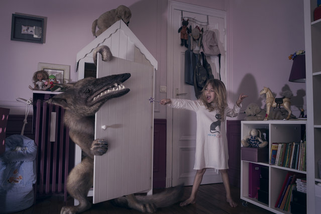 "Charlotte fights a monster with a ""wand"" in her bedroom in Laure Fauvel's ""Terreurs"", 2014, in Paris, France. An imaginative photographer has brought to life monsters that haunt children's nightmares. Armed with sticks, wands and swords the eight and nine year-olds appear to be getting the upper-hand against the villains. Parisian photographer Laure Fauvel, 22, said: I wanted the children not be victims and to fight the monsters. (Photo by Laure Fauvel/Barcroft Media)"