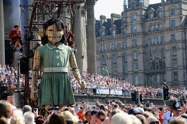 Crowds watch as The Little Giant Girl walks through the streets of Liverpool on July 25, 2014 in Liverpool, England. French street theatre company Royal de Luxe are putting on a show throughout the city as part of Liverpool's World War I centenary commemorations from July 23-27. (Photo by Christopher Furlong/Getty Images)