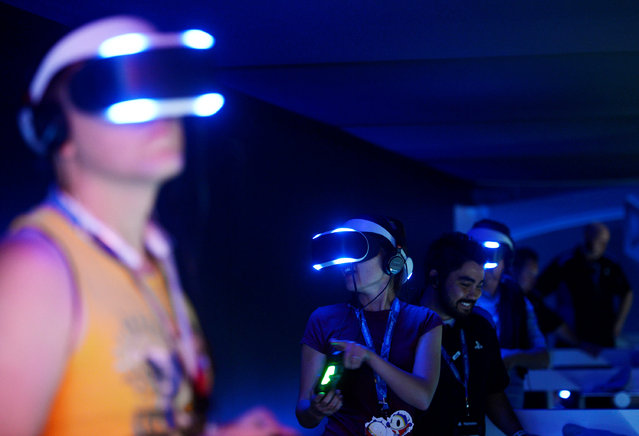 Attendees try out Sony's Project Morpheus VR headset at the 2014 Electronic Entertainment Expo, known as E3, in Los Angeles, California, June 11, 2014. (Photo by Kevork Djansezian/Reuters)