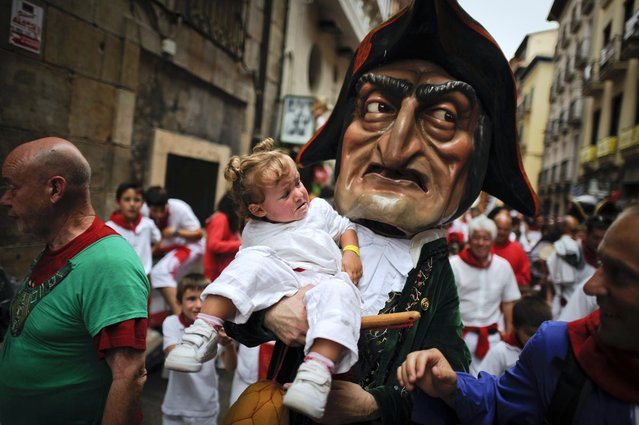 A man dressed as a giant holds a young girl during the giants and big heads parade of the San Fermin festival