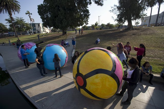 "Volunteers wait by inflated spheres to be lowered into MacArthur Park Lake during the installation of Portraits of Hope's exhibition ""Spheres at MacArthur Park"" in Los Angeles, California August 21, 2015. (Photo by Mario Anzuoni/Reuters)"