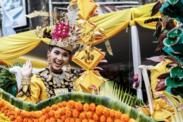 A participant waves to the crowd during Tomohon International Flower Festival on August 8, 2014 in Tomohon, North Sulawesi, Indonesia. The flower festival is a biannual event that has run since 2008. It was originally devised to boost tourism in the North Sulawesi region. (Photo by Putu Sayoga/Getty Images)