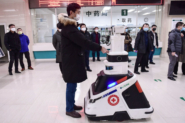 This photo taken on February 26, 2020 shows a patrol robot – used to check temperatures, identities and disinfect people – checking the identity of a visitor at a hospital in Shenyang in China's northeastern Liaoning province. The hospital uses the robot to reduce the pressure on front-line medical staff and to avoid cross infections from the COVID-19 coronavirus. (Photo by AFP Photo/China Stringer Network)