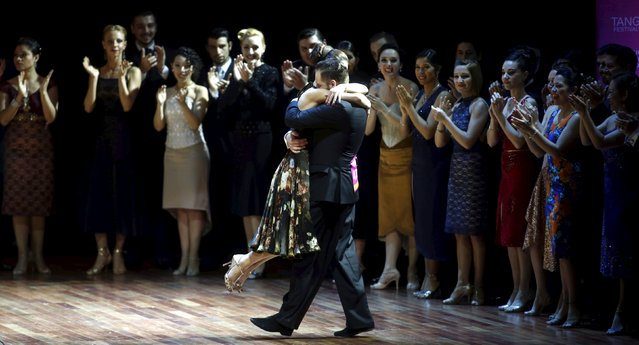 Maksim Gerasimov and Maria Marinova from Russia, representing the city of Saint Petersburg, embrace as other competitors applaud after they placed fourth at the Tango World Championship in Salon style in Buenos Aires, Argentina, August 26, 2015. (Photo by Marcos Brindicci/Reuters)