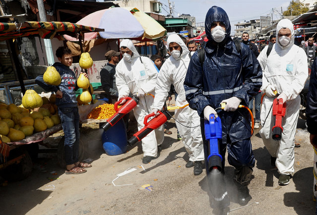 Workers wearing protective gear spray disinfectant as a precaution against the coronavirus, at the main market in Gaza City, Thursday, March 19, 2020. The Middle East has some 20,000 cases of the virus, with most cases in Iran or linked to travel from Iran. The vast majority of people recover from COVID-19. (Photo by Adel Hana/AP Photo)