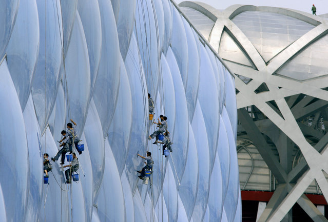 A worker walks atop the roof of the National Stadium (R), also known as the Bird's Nest, as cleaners abseil down the exterior of the National Aquatics Center, also known as the Water Cube, at the Olympic Green in Beijing July 17, 2008. (Photo by David Gray/Reuters)