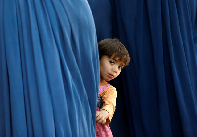 An Afghan girl holds her mother's burqa as she waits to receive aid from the Afghanistan Chamber of Commerce and Industries (ACCI) during the month of Ramadan in Kabul, Afghanistan June 23, 2016. (Photo by Mohammad Ismail/Reuters)