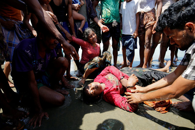 A Rohingya refugee woman cries as her relative lost consciousness after a boat capsized on the shore of Shah Porir Dwip while crossing the Bangladesh-Myanmar border in Teknaf, Bangladesh, September 14, 2017. (Photo by Mohammad Ponir Hossain/Reuters)