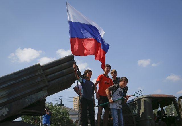 Children holding a Russian flag pose for photos on a destroyed Ukrainian army Grad multiple rocket launcher system that was seized and put on public display at the central square in Donetsk August 24, 2014. (Photo by Maxim Shemetov/Reuters)