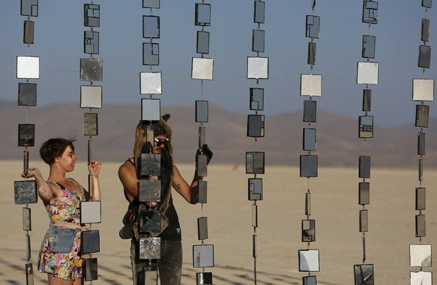 """Denise S., (L) and Richard S. utilize an art installation during the Burning Man 2015 """"Carnival of Mirrors"""" arts and music festival in the Black Rock Desert of Nevada, August 31, 2015. (Photo by Jim Urquhart/Reuters)"""