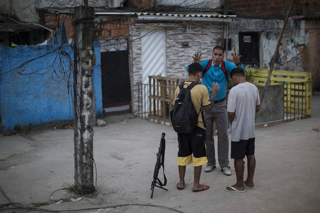 In this July 16, 2016 photo, pastor Nilton blesses two young drug traffickers at a slum in Rio de Janeiro, Brazil. Many of the young drug traffickers have an immense respect for the pastor, a former drug trafficker. It's not uncommon to see young men set their weapons down, but only long enough to receive his blessing. (Photo by Felipe Dana/AP Photo)