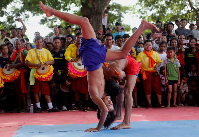 """Cambodian men wrestle during an event that marks the Day of Death, also called the Ancestors' Day (or """"Pchem Ben"""" in Khmer), in Vihear Sour village in Kandal province, Cambodia, 20 September 2017. During the festivities, the villagers organize buffalo and horse races, as well as Khmer traditional wrestling competitions to celebrate their local customs and traditions. (Photo by Kith Serey/EPA/EFE)"""