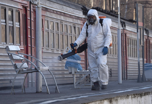 A member from a local veterinary service wearing protective suit sprays disinfectant on a platform of the railway station in Ladozhskoye Ozero village outside St. Petersburg, Russia, Saturday, April 4, 2020. (Photo by Dmitri Lovetsky/AP Photo)