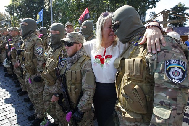 """A woman reacts as she embraces her son, who joined as a new volunteer of the Ukrainian interior ministry's special battalion """"Sich"""", before a ceremony, where he and his comrades will take an oath of allegiance to the country, in Kiev August 26, 2014. (Photo by Valentyn Ogirenko/Reuters)"""