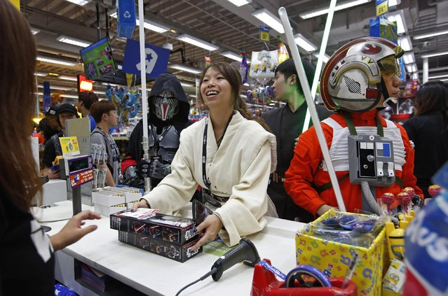 """Fans dressed as Star Wars characters shop at a toy store at midnight in Hong Kong, Friday, September 4, 2015 as part of the global event called """"Force Friday"""" to release new Star Wars toys and other merchandise of the new movie """"Star Wars: The Force Awakens"""". (Photo by Kin Cheung/AP Photo)"""