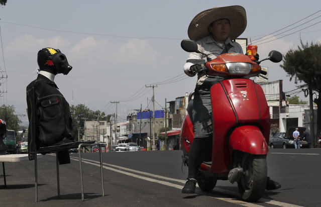 A man rides past a mannequin wearing a gas mask, a wrestling mask and a jean jacket, as a way to advertise his Mexican wrestling mask shop, in Iztapalapa, Mexico City, Thursday, April 9, 2020. The Mexico City government is sending out teams to help the home-bound and the homeless during the shutdown declared to combat the new coronavirus. (Photo by Marco Ugarte/AP Photo)