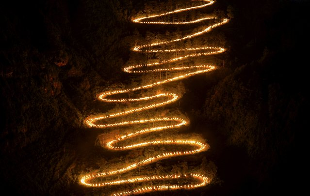 People holding torches walk on a mountain trail during a trekking event to mark the 70th anniversary of the end of World War Two, in Qinglong county, Guizhou province, September 4, 2015. Around 2974 people participated in trekking the trail, through where the American aid to China were transported from Myanmar to China's frontlines during the World War Two, according to local media. (Photo by Reuters/Stringer)