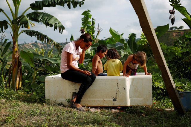 Lisibeht Martinez (L), 30, who was sterilized one year ago, sits next to her children while they play in a bathtub in the backyard of their house in Los Teques, Venezuela July 19, 2016. (Photo by Carlos Garcia Rawlins/Reuters)