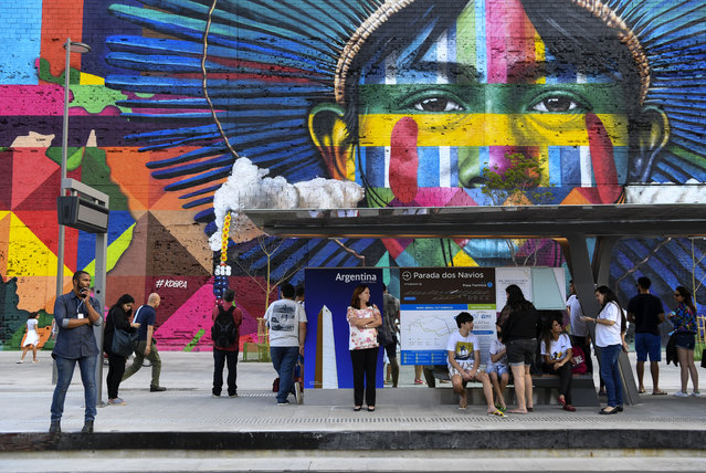 People wait for the new metro line train in the city center with a mural by the artist Kobra on August 2, 2016 in Rio De Janeiro, Brazil. (Photo by Jonathan Newton/The Washington Post)
