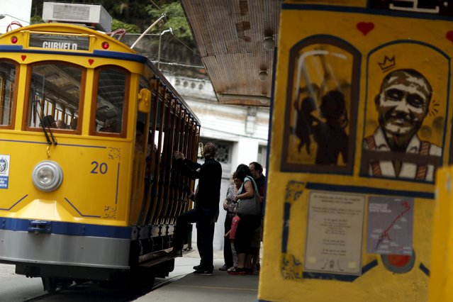 Passengers board the bonde, the typical tram line in Santa Teresa neighborhood, in Rio de Janeiro, Brazil, September 9, 2015. (Photo by Pilar Olivares/Reuters)