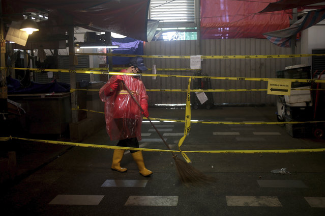 A worker cleans a wet market closed during the restricted movement order due to the outbreak of the coronavirus disease (COVID-19) outside of Kuala Lumpur, Malaysia, on Wednesday, March 25, 2020. The Malaysian government issued a restricted movement order to the public for the rest of the month to help curb the spread of the new coronavirus. (Photo by AP Photo/Stringer)